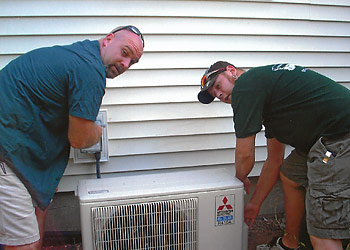 Technicians installing Mr. Slim ductless cooling and heating system